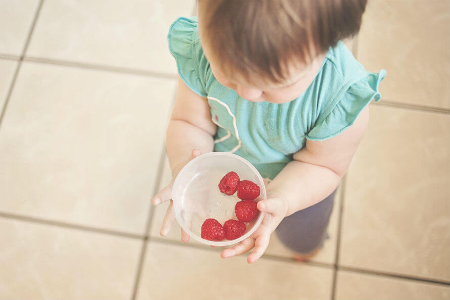 A toddler holding a bowl filled with raspberries