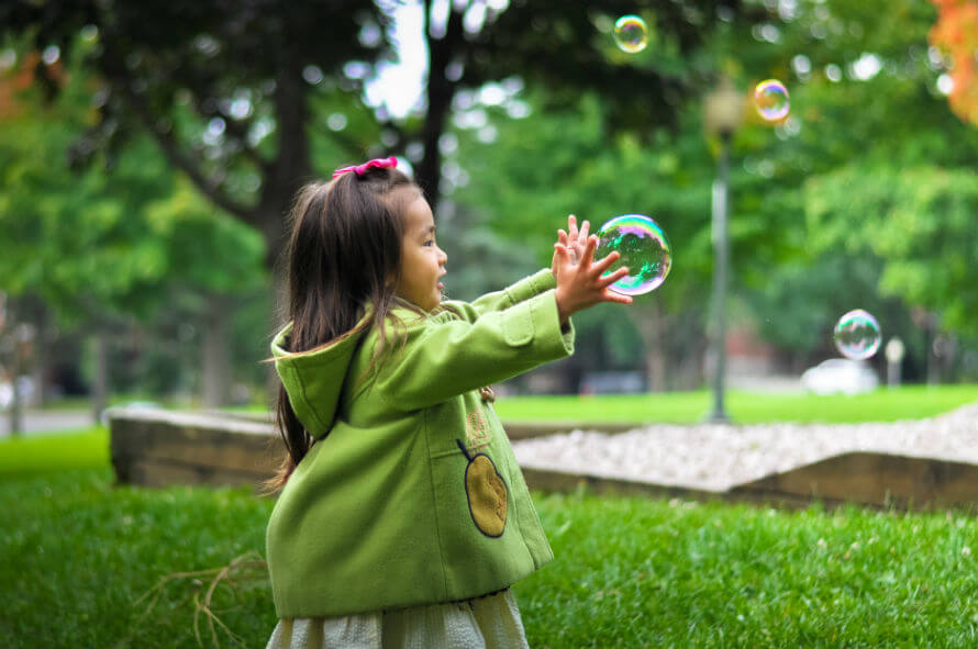 A young girl outside chasing bubbles