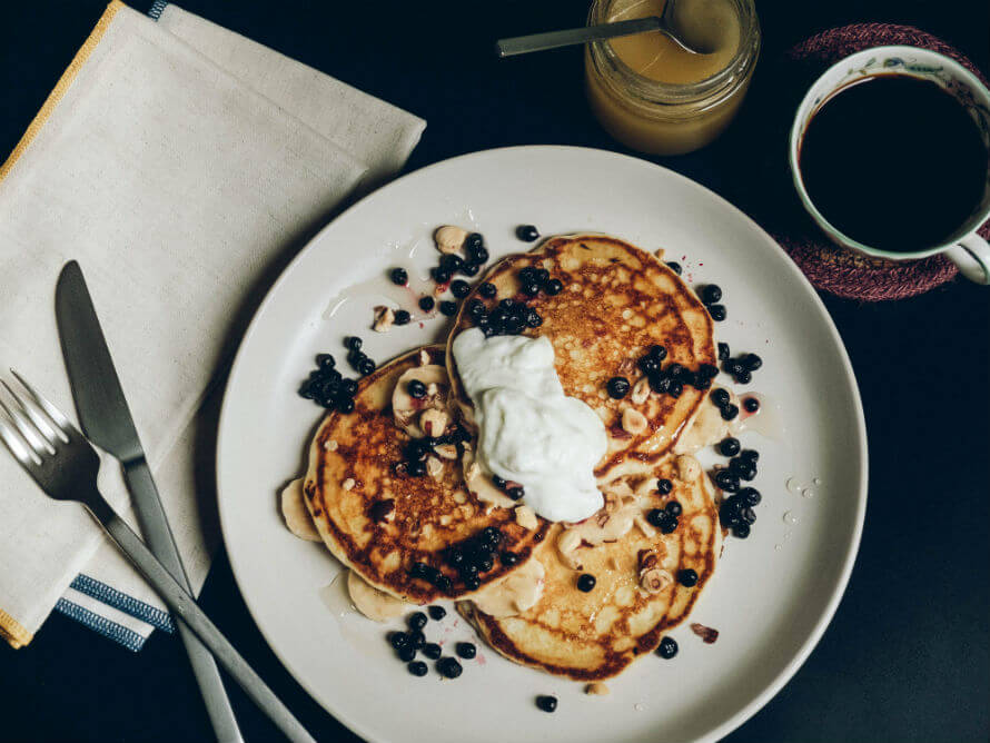 A plate of homemade gluten-free pancakes topped with yogurt, blueberries, hazelnuts and honey beside a cup of coffee and a jar of honey