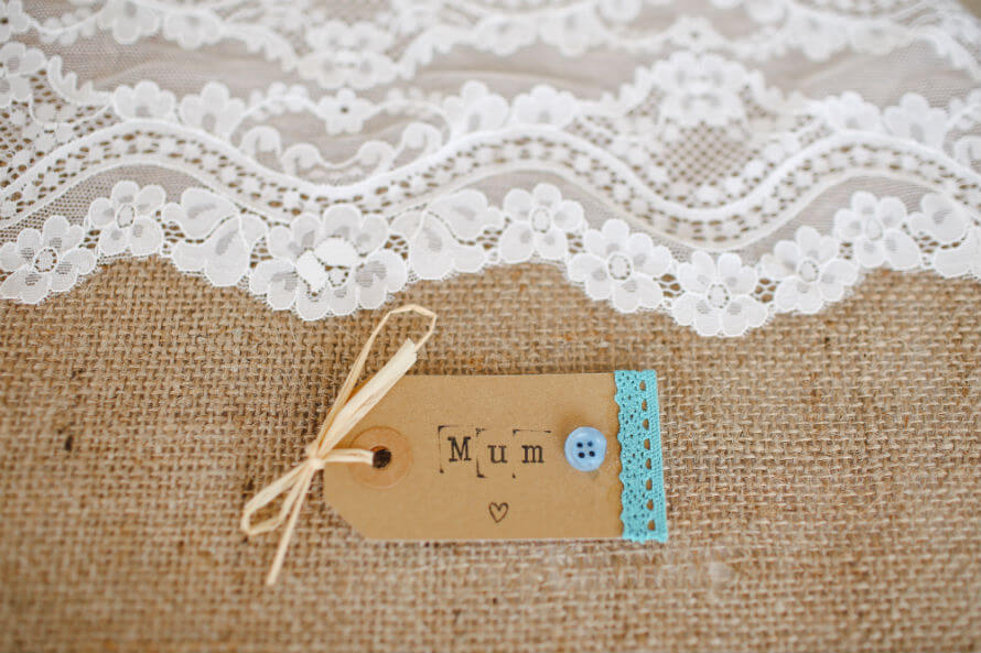 "A tag printed with the word ""mum"" on a canvas background underneath white lace"