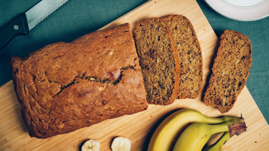 Loaf of sprouted banana bread on a chopping board next to bananas and bread knife