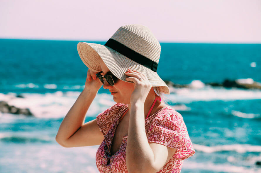 Woman walking on beach wearing sunglasses and sun hat