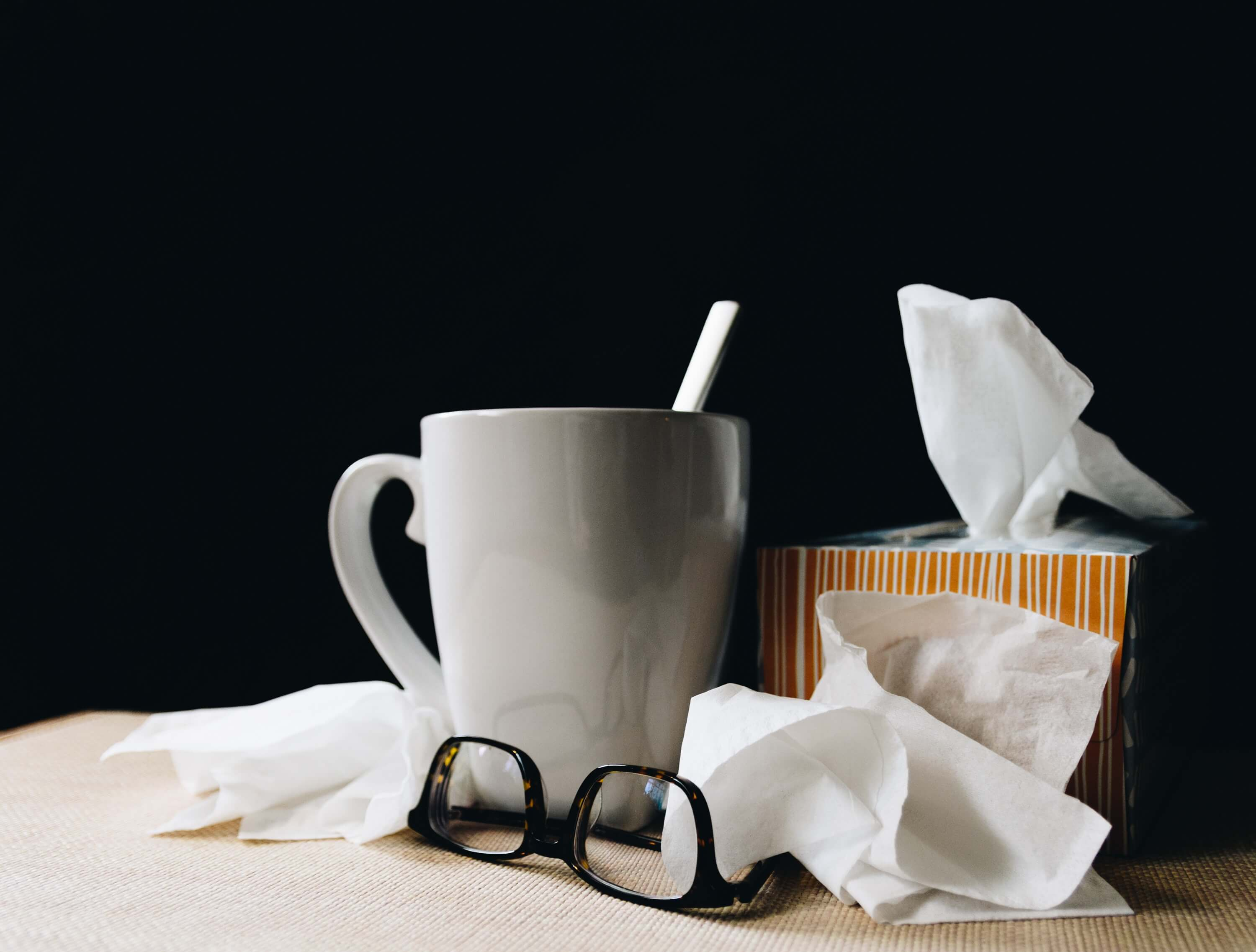 Tissue box, hot drink and glasses