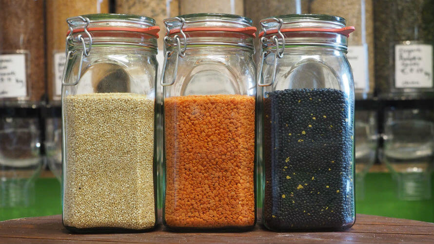 Glass jars filled with legumes and grains in Organico's zero-waste bulk shopping area