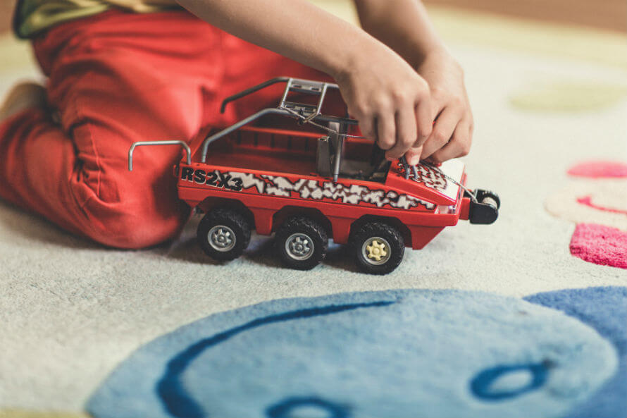 Hands of boy playing on floor with toy car