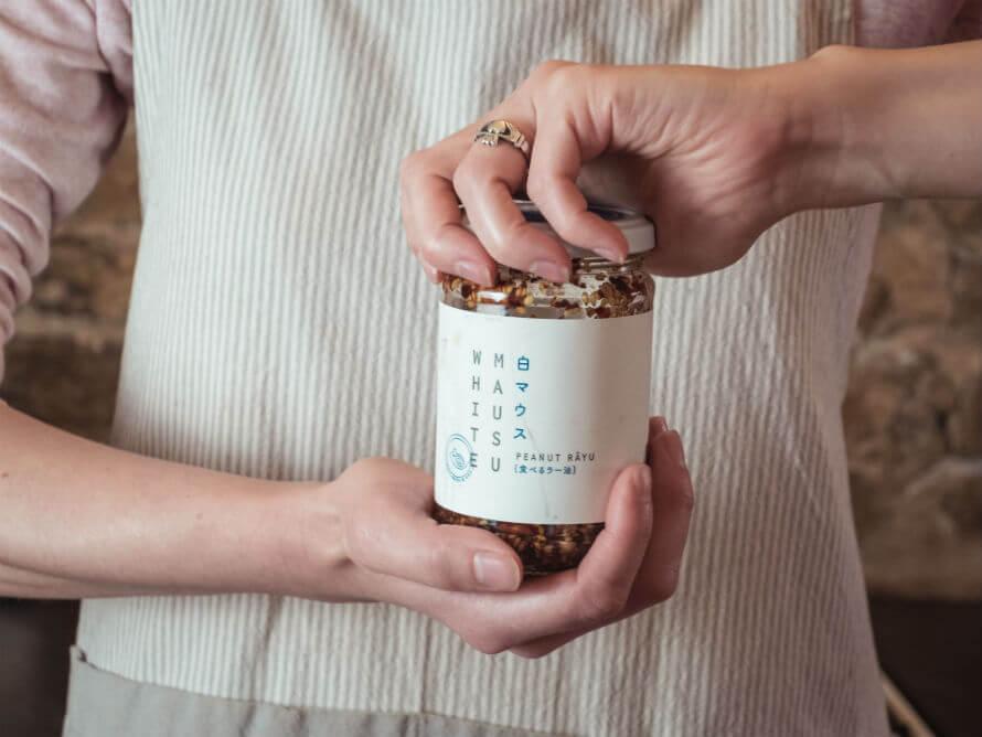 Woman opening a jar of Peanut Rayu