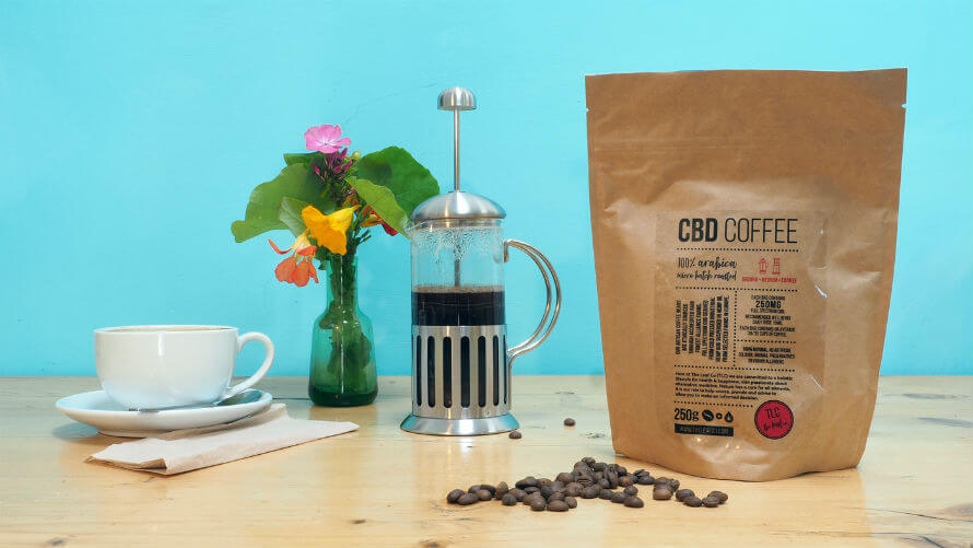 A bag of CBD coffee, a French press, a flower arrangement and a cup and saucer