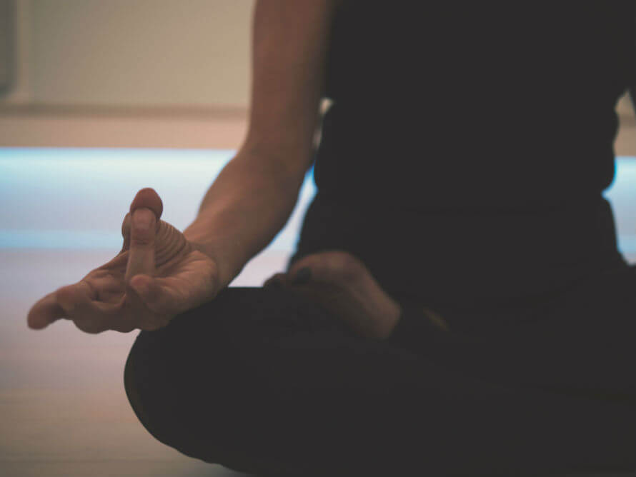 Torso and legs of woman sitting on floor in cross-legged position practicing yoga