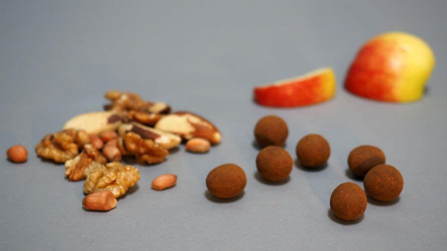 Piles of raw nuts, coated hazelnuts, and an apple with a slice taken out
