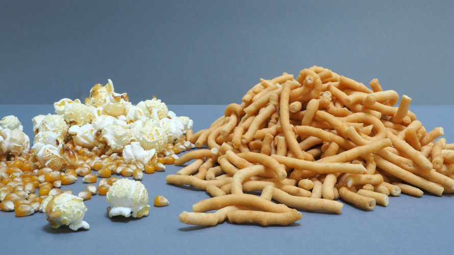 Piles of popped popcorn and kernels and sesame sticks