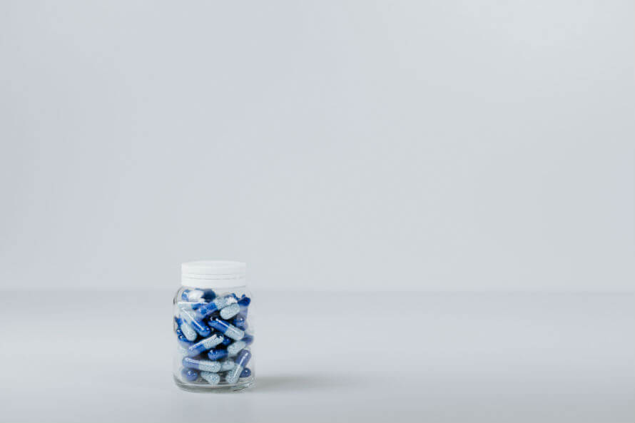 Clear bottle of pills on a white background