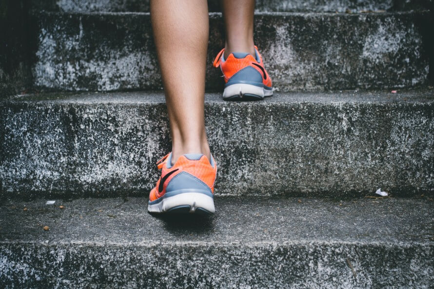 Woman's legs running up concrete stairs in running shoes